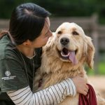 A Women Holds Her Dog and looking at dogs Face